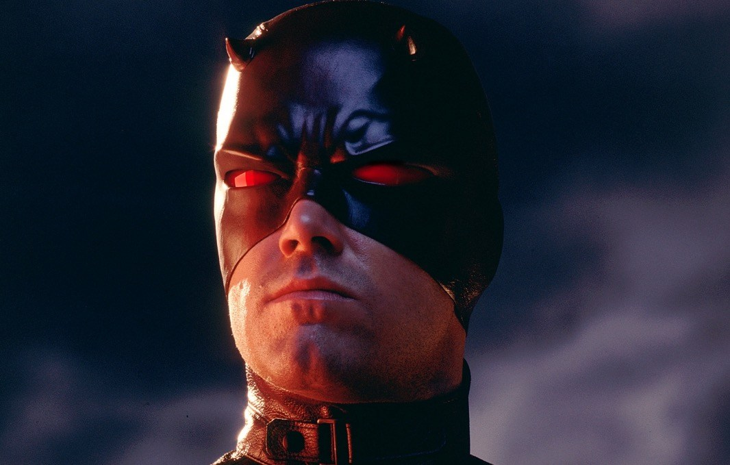 Ben Affleck as Daredevil, wearing a leather red mask and looking sternly off into the distance