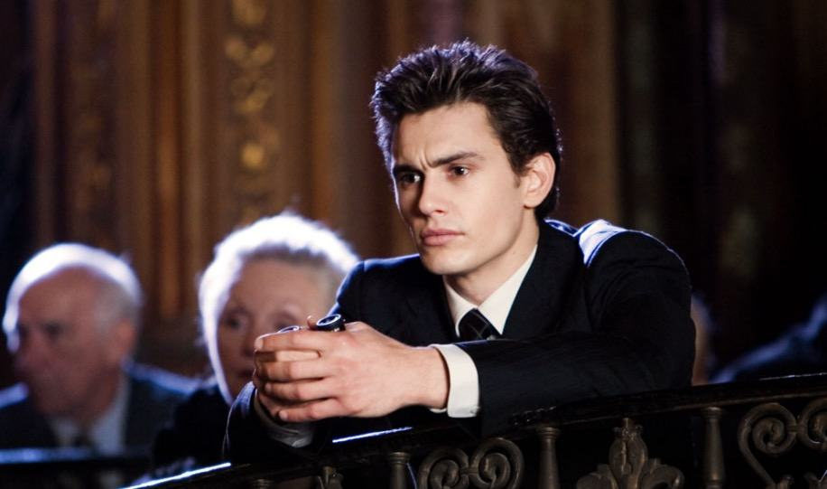 James Franco, wearing a suit, looking off to the left of the frame, and leading forward against a railing