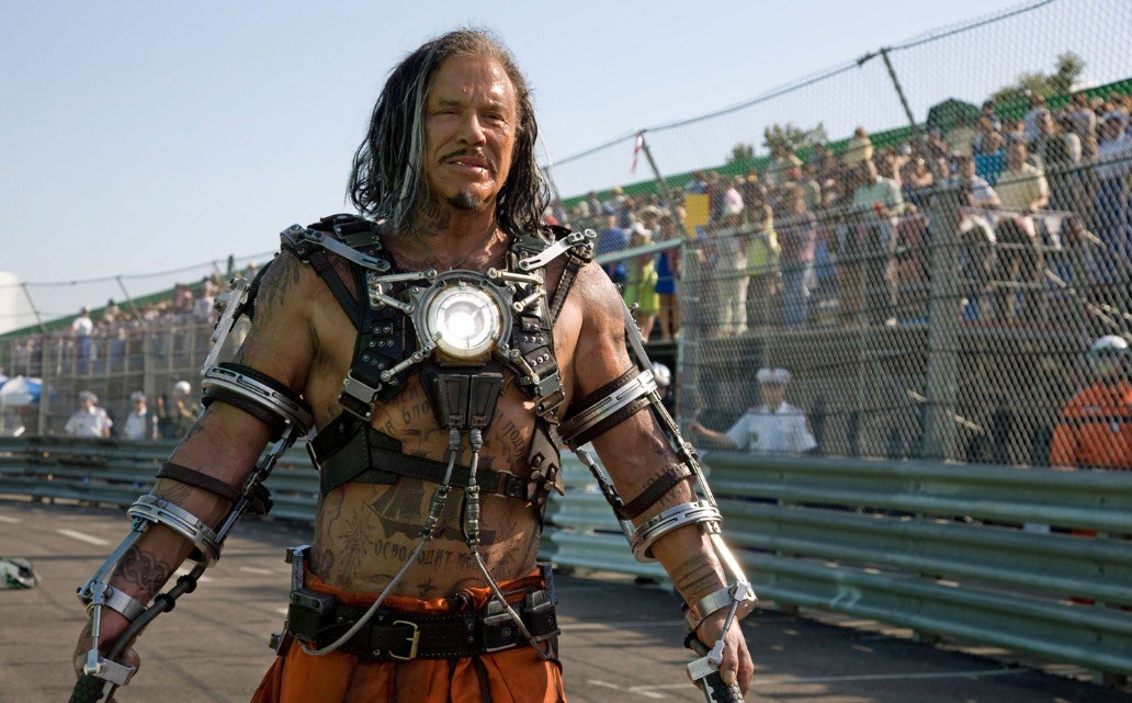 Mickey Rourke, in a metal vest with a luminescent battery in the center, holding electric whips in either hand