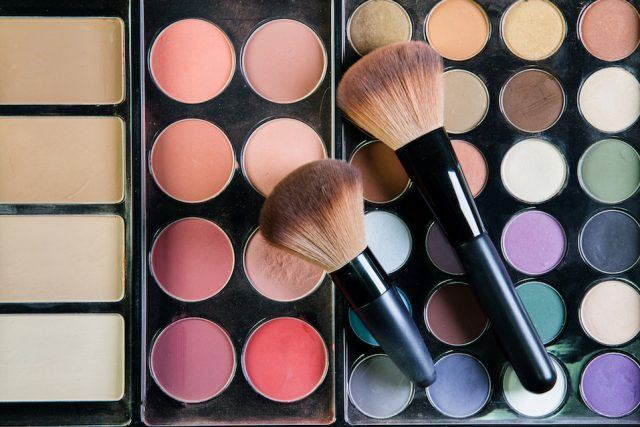 a palette of nude colored eyeshadows and colorful pigments on a wooden background