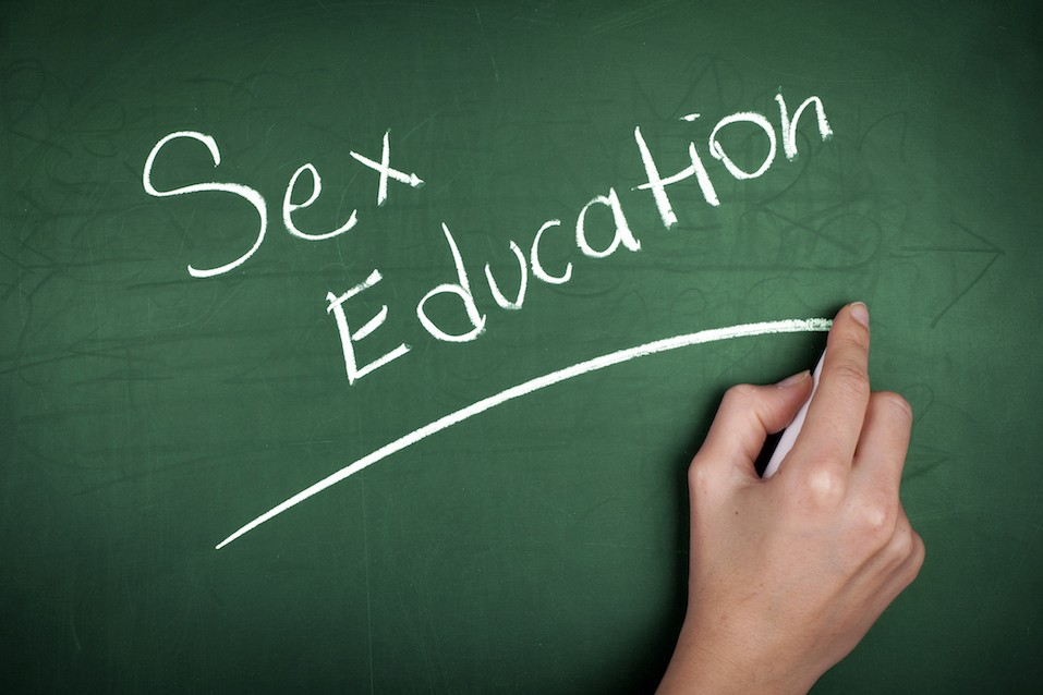 "Woman hand-writing ""Sex Education"" on green blackboard"