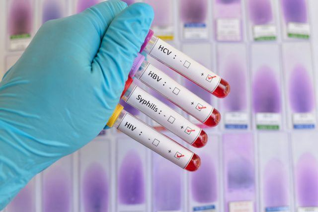 A doctor holds blood samples in a lab.
