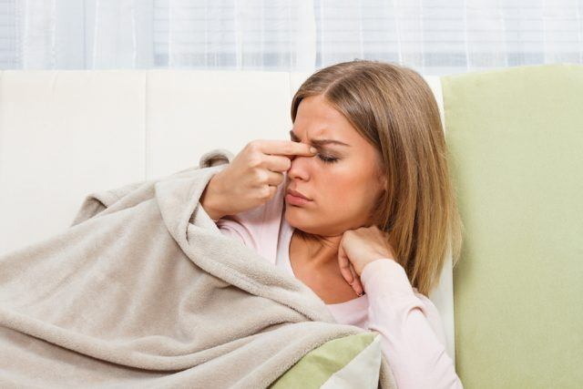 A woman holds her nose during a sinus infection.