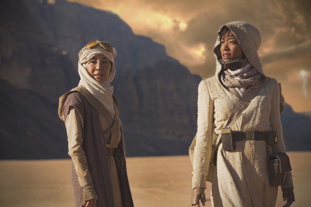Sonequa Martin-Green as First Officer Michael Burnham and Michelle Yeoh as Captain Philippa Georgiou stand in a desert landscape dressed in robes.