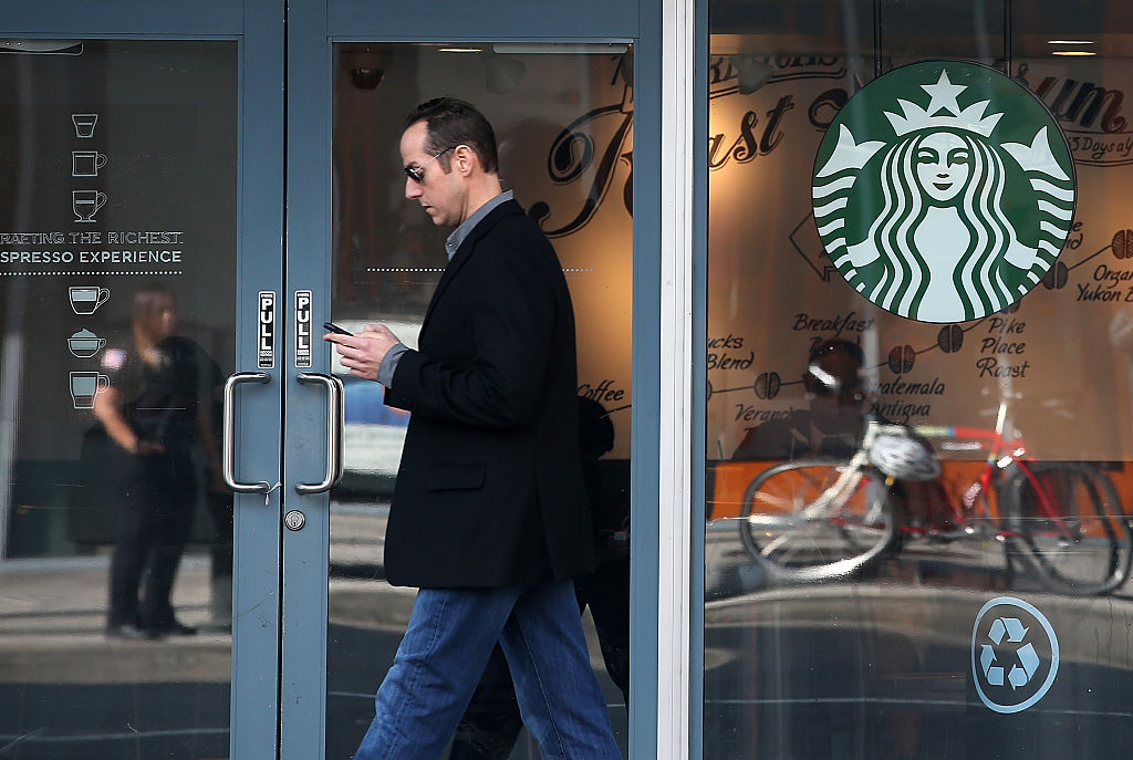 man walks outside a starbucks