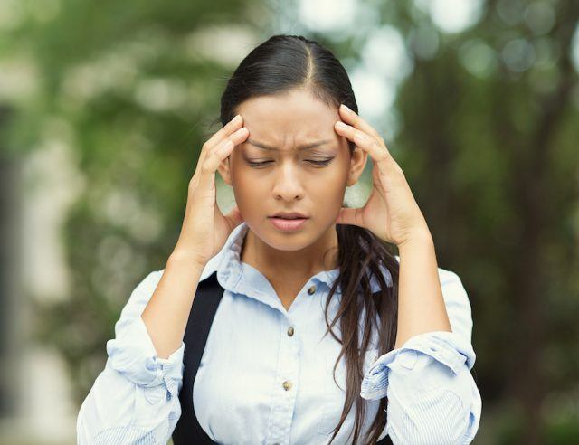 Stressed woman holds her forehead.