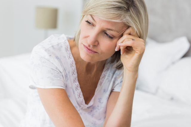 Tensed mature woman sitting on bed.