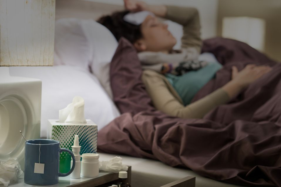 Tissue, flu medicines and tea on bedside table sick woman