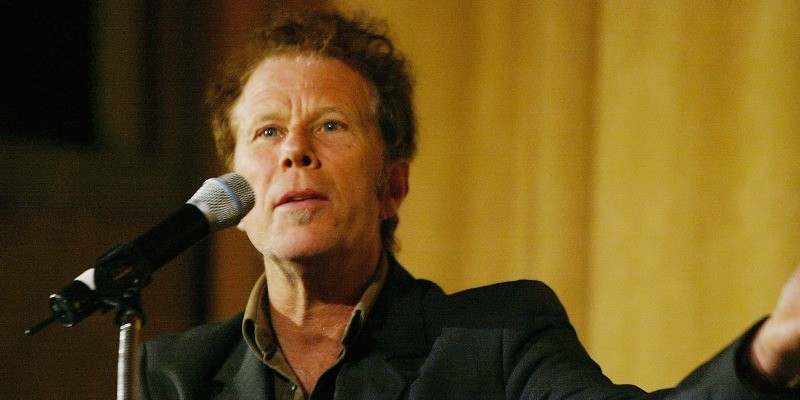 Tom Waits stands in front of a microphone and holds his arm out.