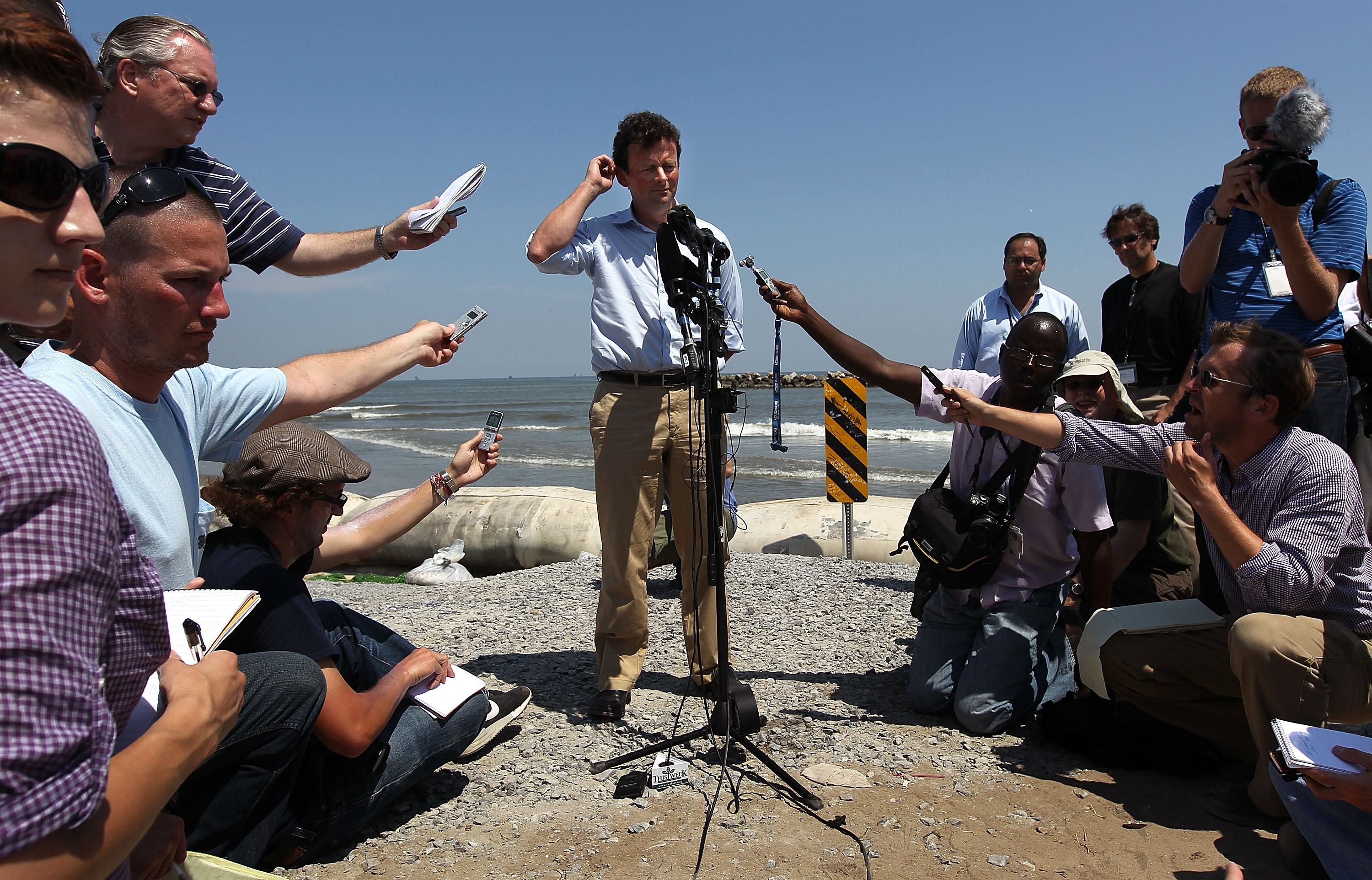 Former BP CEO Tony Hayward answers questions from the media on an oil-stained beach.