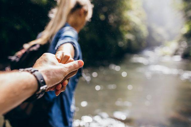 man and woman holding hands while crossing the creek