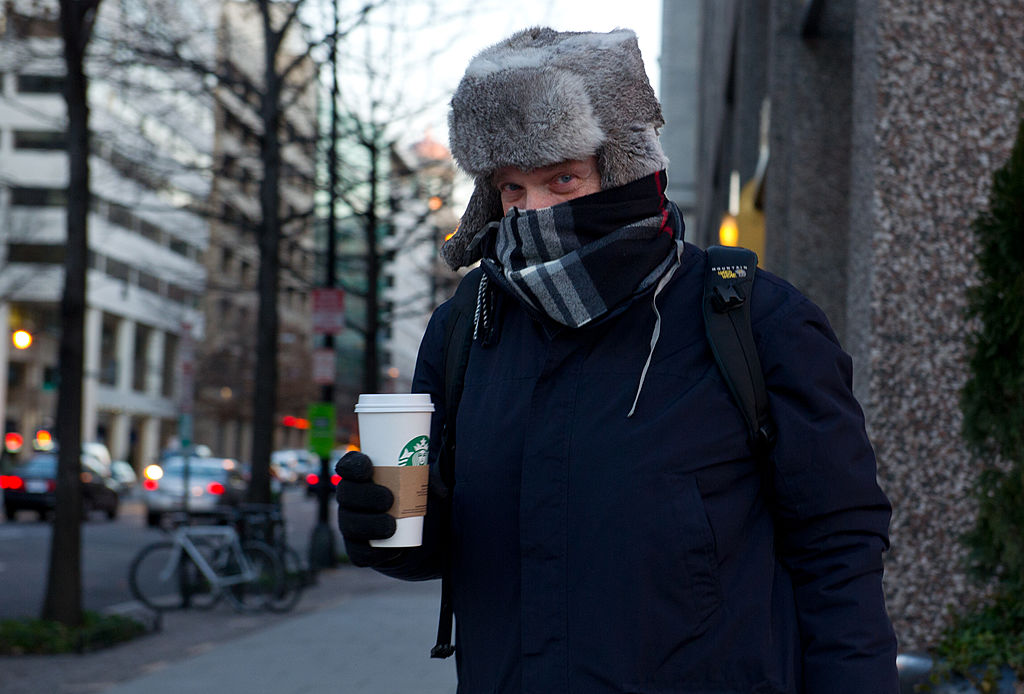 man in winter clothing with a starbucks cup
