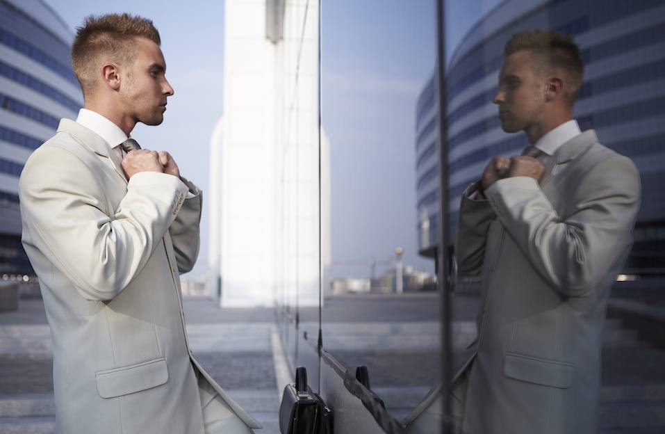 Vain business man checking his looks in mirror