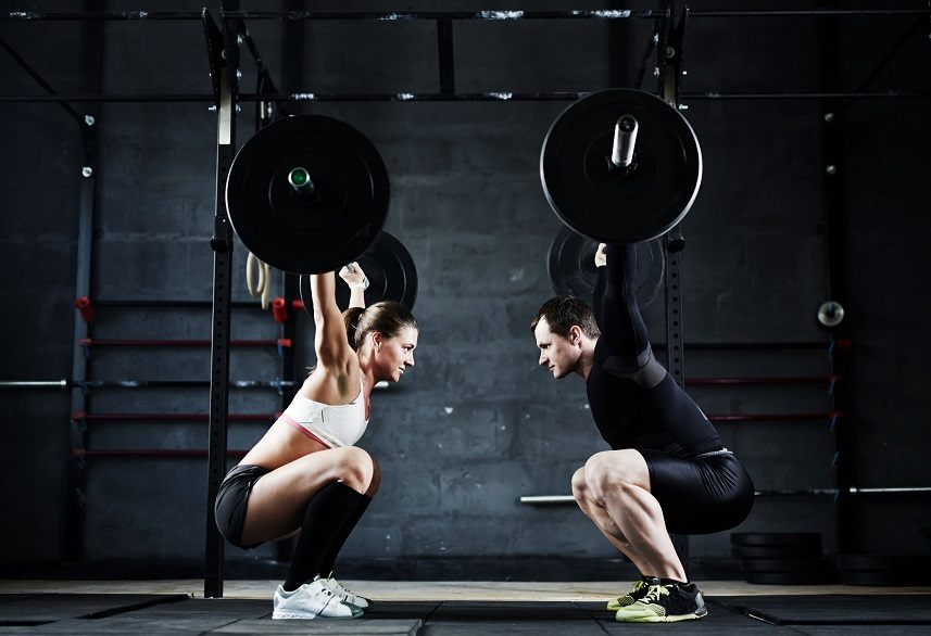 Young man and woman holding huge heavy barbells