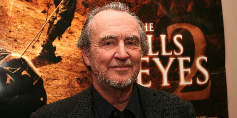 Wes Craven stands in front of a 'The Hills Have Eyes 2' poster.