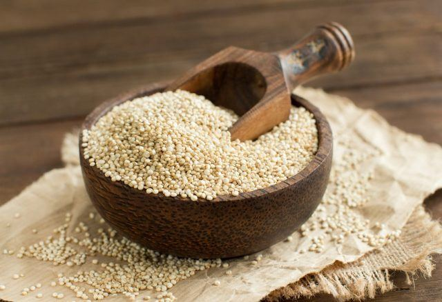 White quinoa in a bowl with wooden scooper.