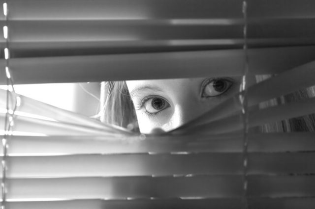 female looking through window blinds