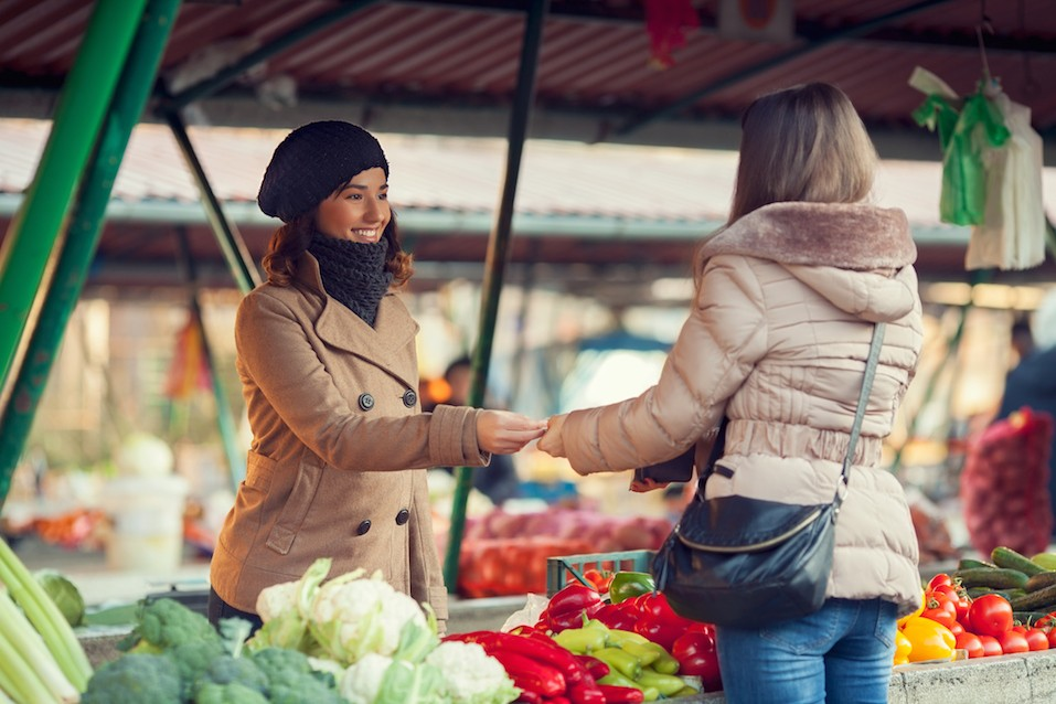 woman in coat buying produce