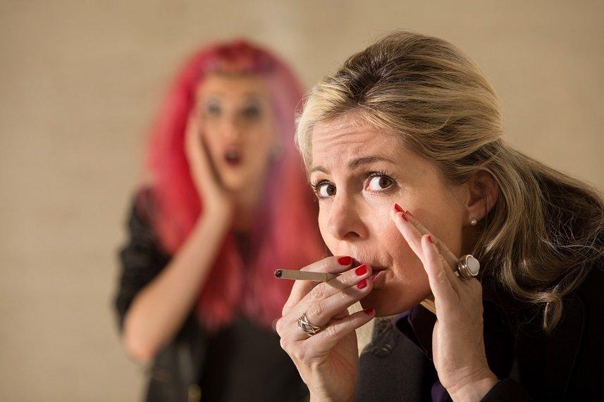 Surprised teen behind woman smoking a cigarette