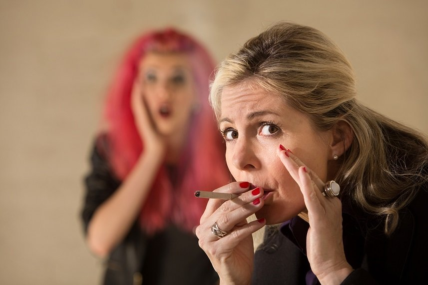 Surprised teen behind woman smoking a cigarette