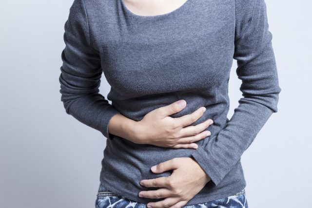 Woman holds her stomach in pain.