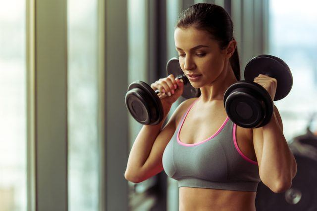 Active young woman working out with dumbbells in gym.