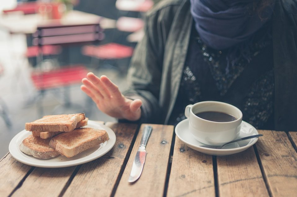 a woman sitting at a table refusing bread with coffee in front of her