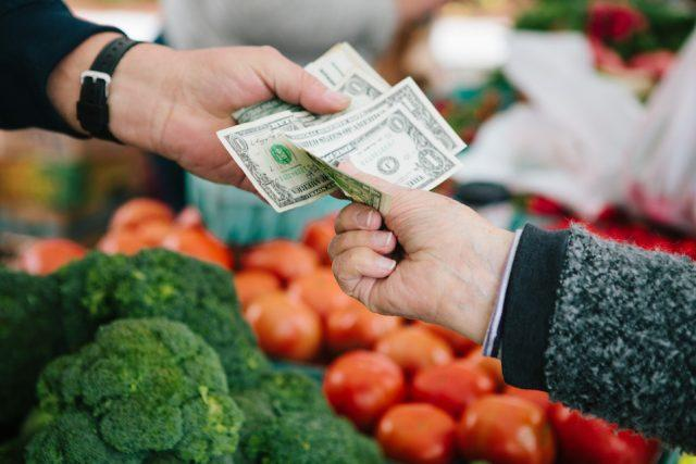 Woman pays for fresh produce at local farmer's market.