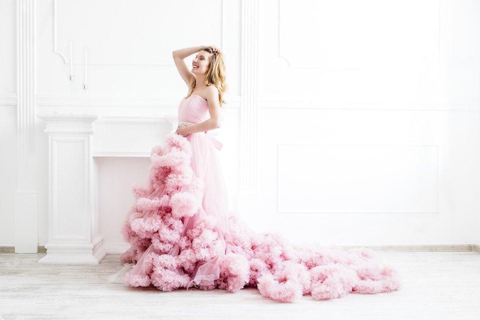 Woman portrait in a long pink dress on white