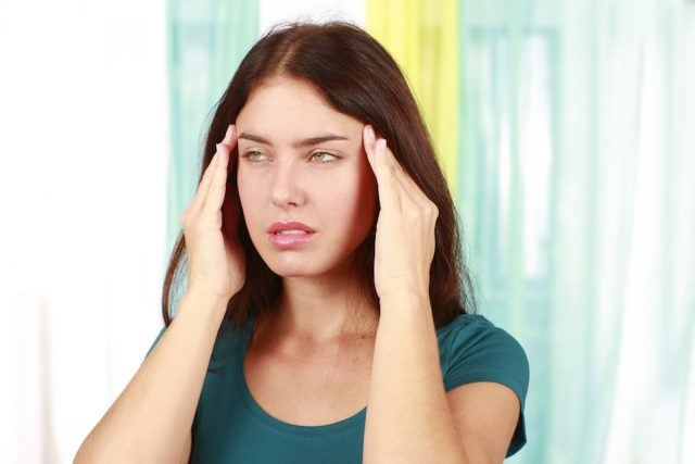 Woman suffering from migraine with her hands on her forehead