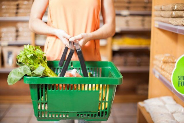 woman holding a basket full of groceries