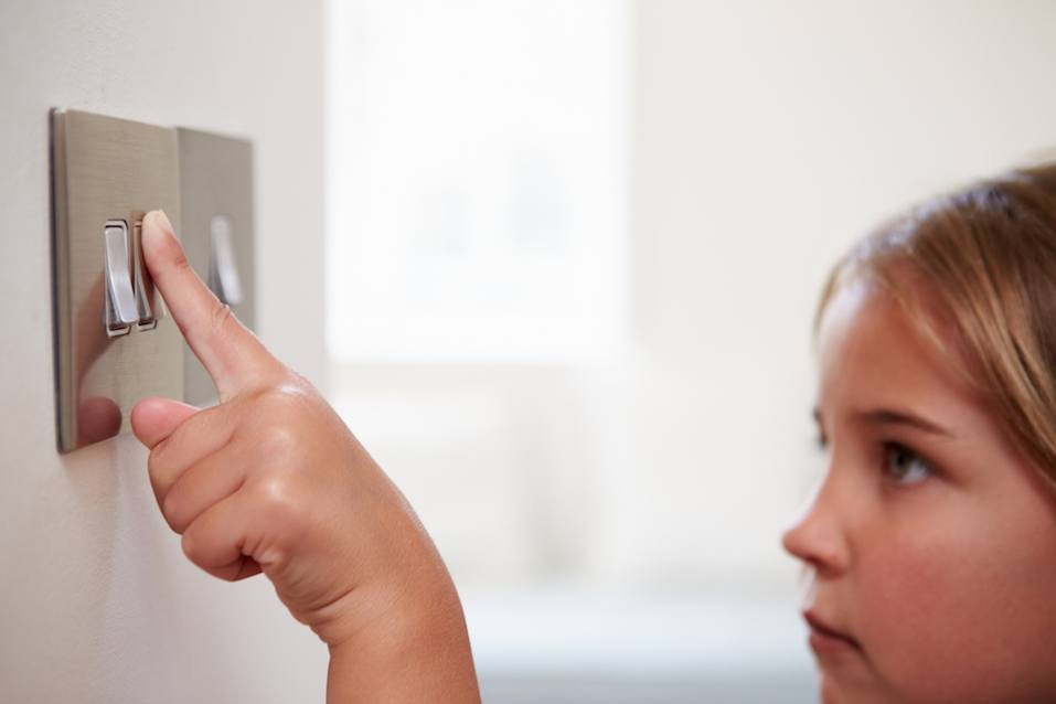girl turning on light switch