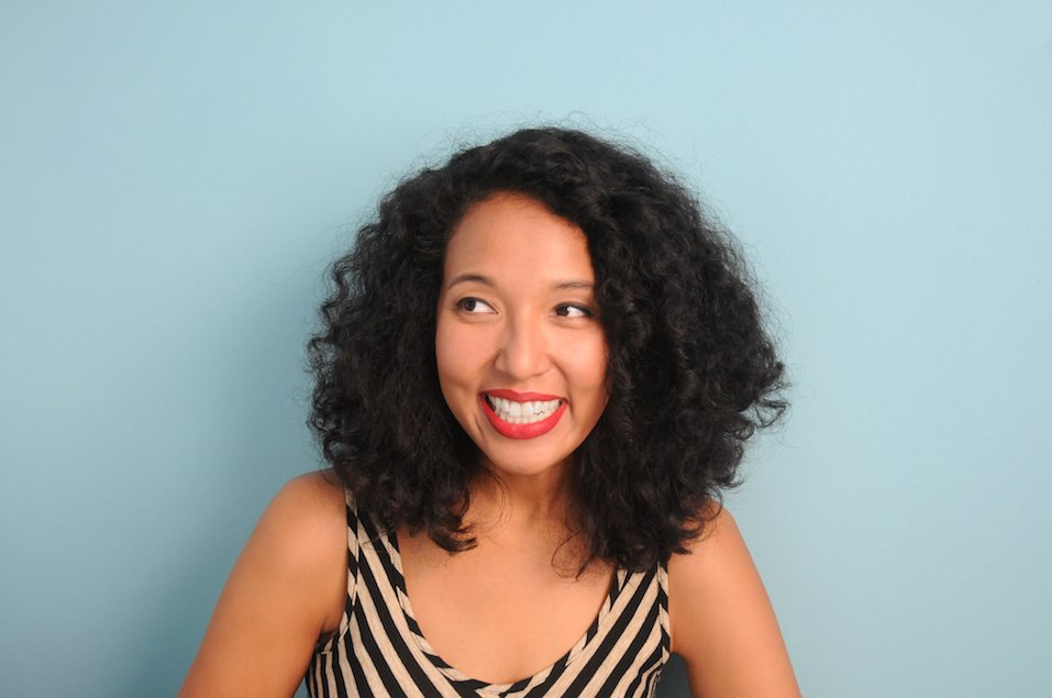 A young, mixed race woman smiling