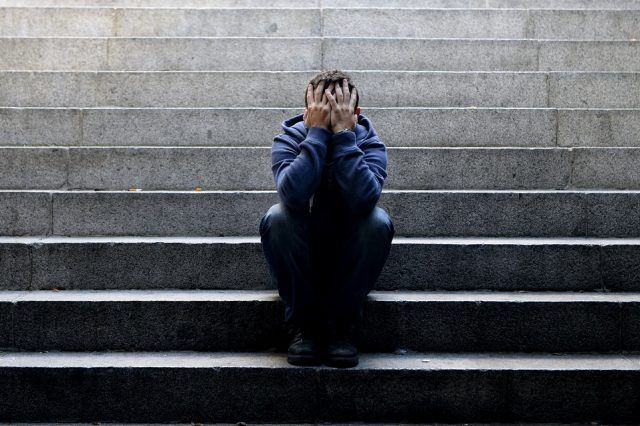 A man sits on the steps of a staircase with his head in his hands.