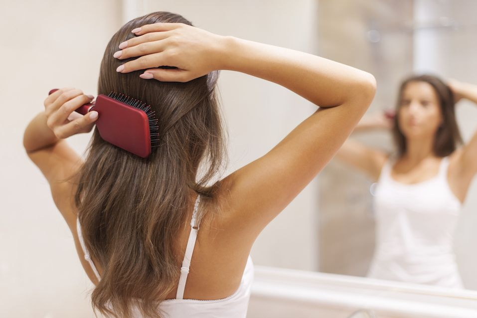 Young woman brushing hair in front of a mirror