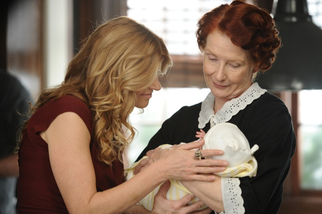 Housekeeper Moira holds an infant as mother Vivien touches and looks at him