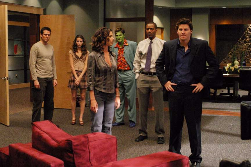 The cast of Angel stands together in a nice office