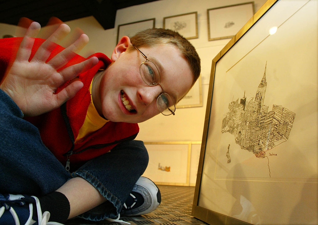 A young man with autism poses among his drawings
