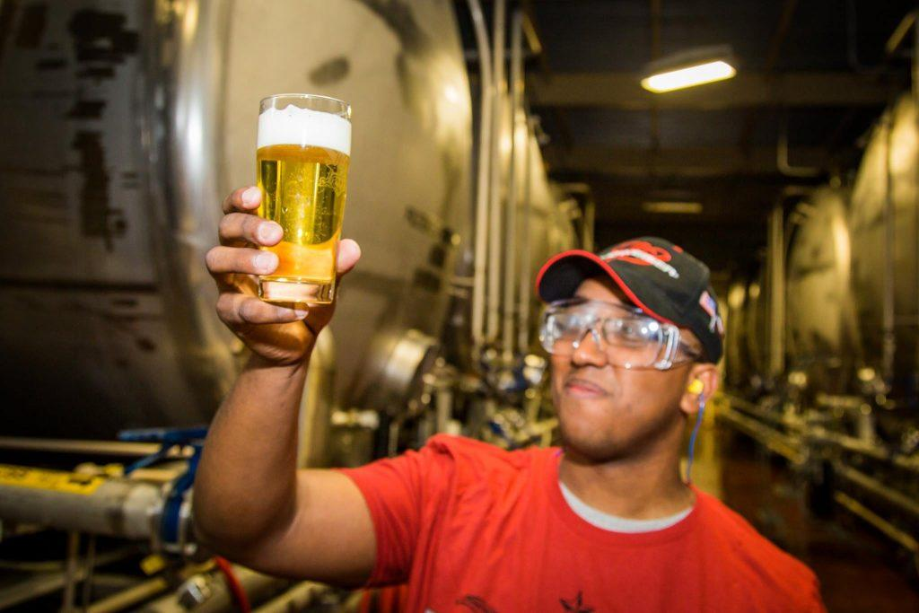 worker holds up beer