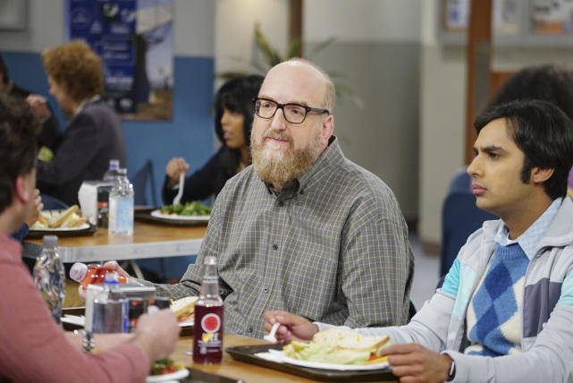 Bert and Raj sit next to each other at a lunch table in a cafeteria in The Big Bang Theory