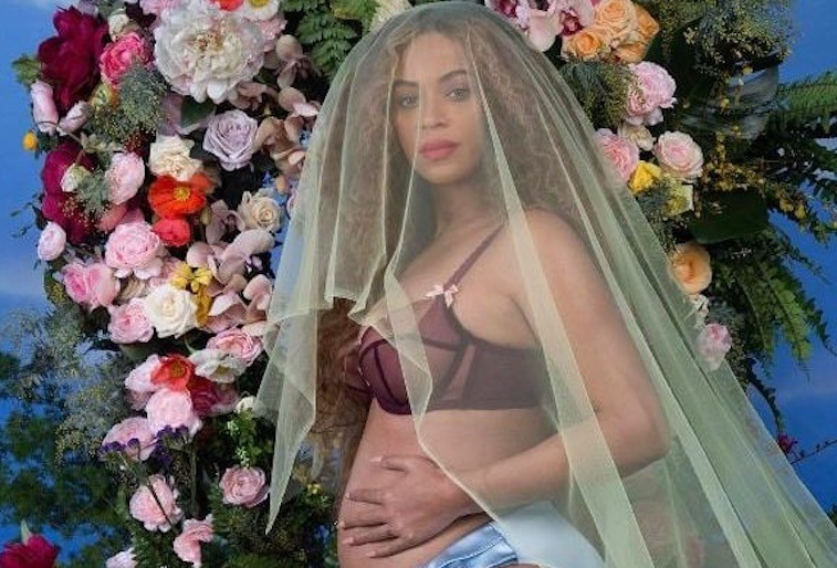 Beyonce holds her pregnant belly while wearing bra and underwear in front of awall of flowers
