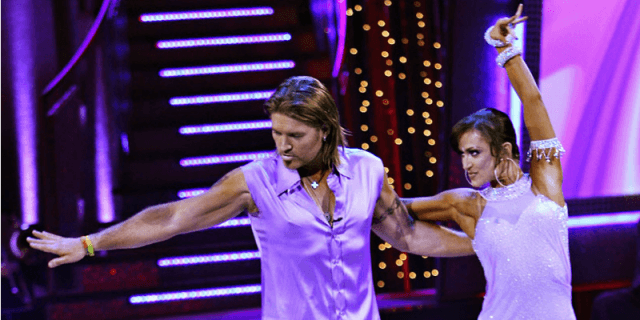 Billy Ray Cyrus and Karina Smirnoff are dancing with their arms stretched out while wearing purple outfits.