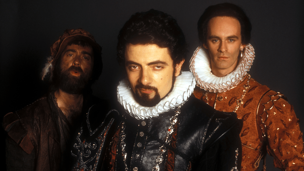 The cast of Blackadder in medieval costumes staring ahead