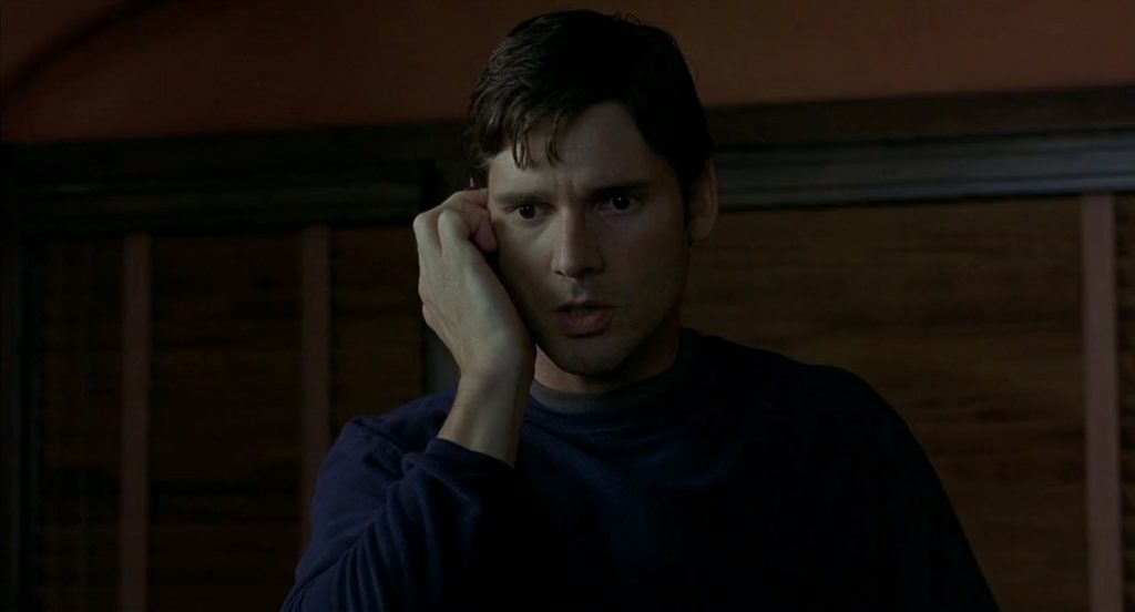 Eric Bana, holding his hand up to the right of his face, looking concerned
