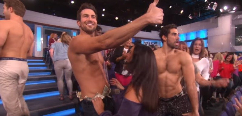 Bryan is stripping on The Ellen DeGeneres Show and is giving a thumbs up.