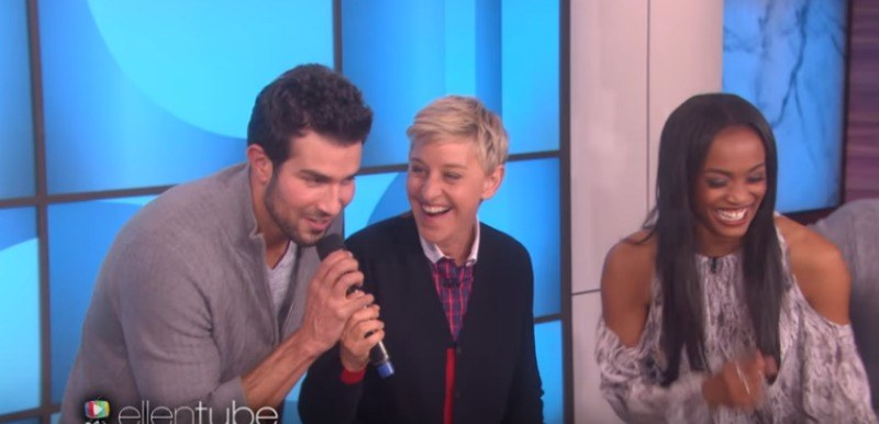 Bryan is taking the microphone from Ellen DeGeneres and Rachel Lindsay is laughing.
