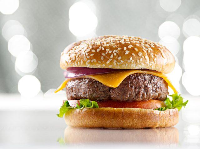 A burger with cheese on a white table with bright lights overhead.