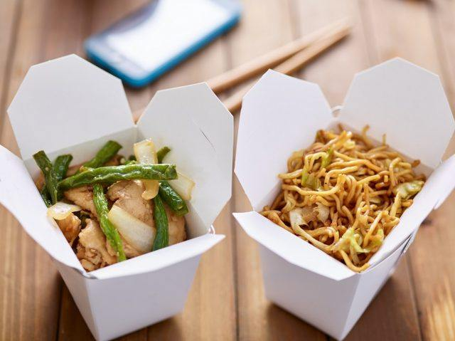 Chinese take out food in boxes on a wooden table.
