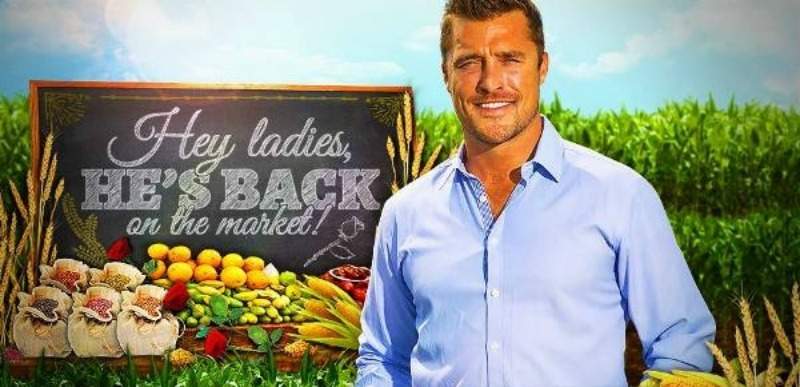 "Chris Soules stands in front of a famer's market and a sign that says, ""hey ladies, he's back."""