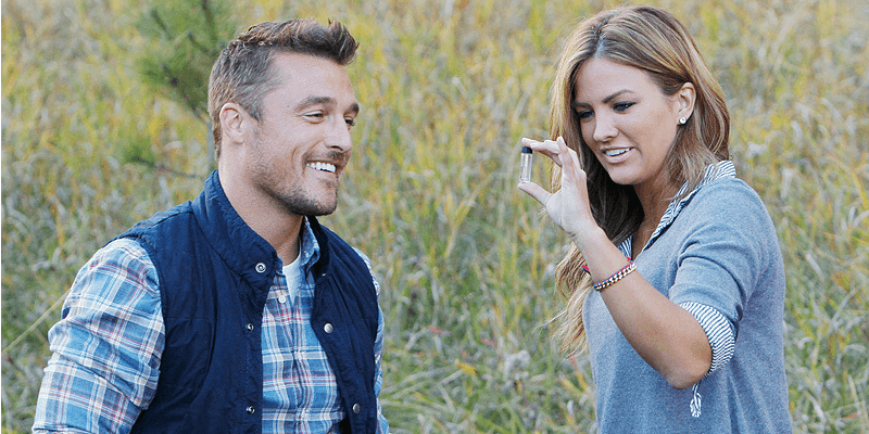 Chris Soules and a woman are looking at a tube while in a field.